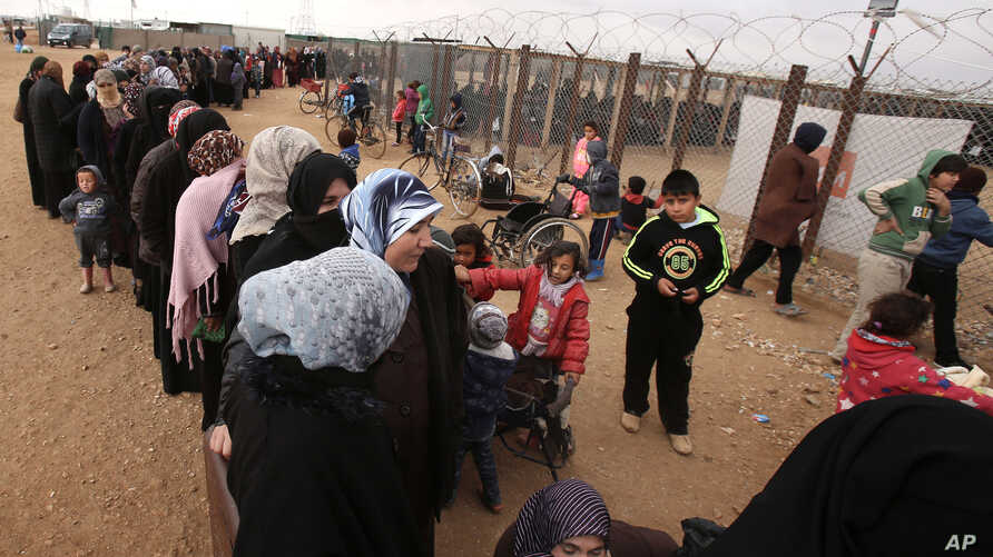 Syrian women wait in line to receive winter aid as UN General Assembly President Mogens Lykketoft visits Zaatari refugee camp in Mafraq, Jordan, Jan. 20, 2016.