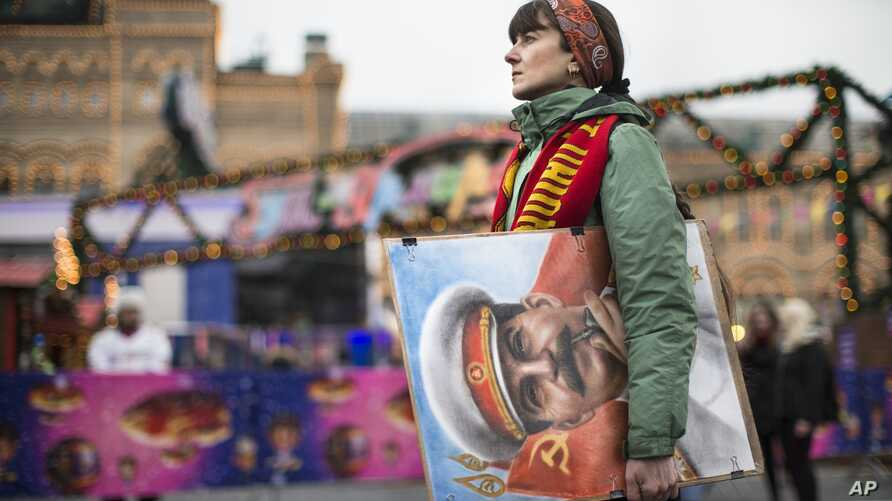 FILE - An artist holds a portrait of former Soviet leader Josef Stalin as Communist Party supporters marking the anniversary of Stalin's birth outside the GUM department store, decorated with New Year and Christmas illumination, in Moscow's Red Squar
