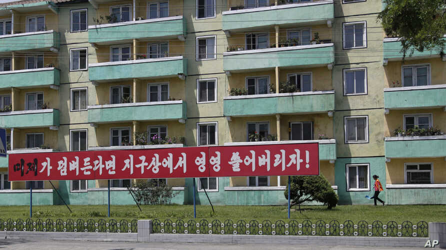 FILE - A woman walks outside an apartment building where an anti-U.S. propaganda banner is put up in Pyongyang, North Korea, June 21, 2018 photo.