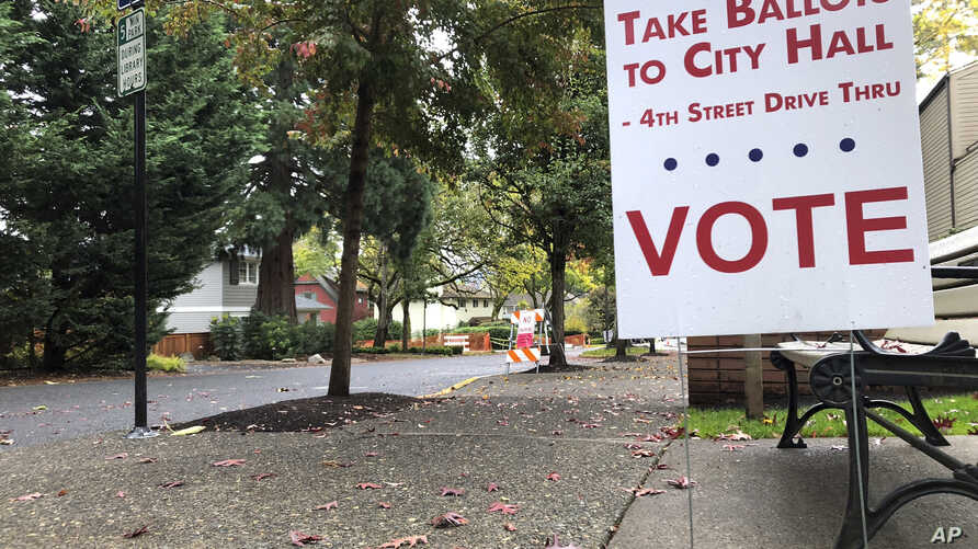 A sidewalk sign directs voters where to go in front of the library in Lake Oswego, Oregon, Oct. 31, 2018.