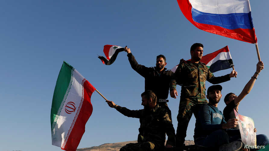 Syrians wave Iranian, Russian and Syrian flags during a protest against U.S.-led air strikes in Damascus, Syria April 14,2018.