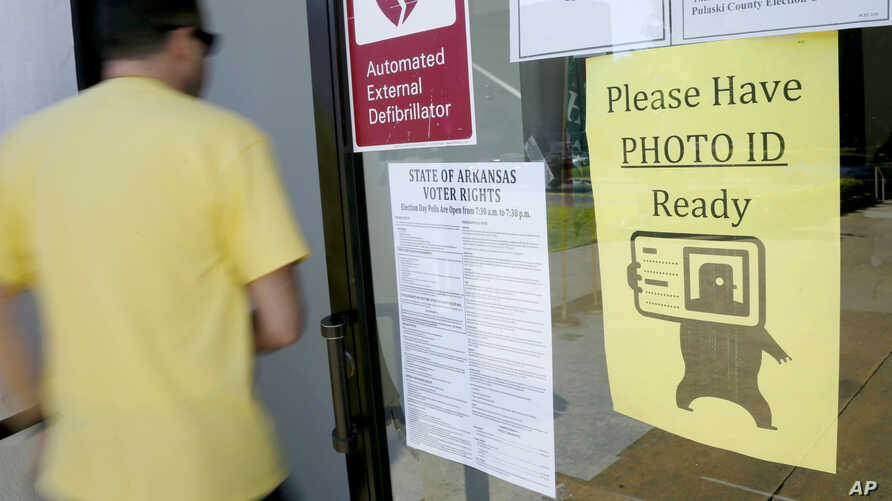"""A voter walks past a """"Please Have Photo ID Ready"""" sign as he enters an early-voting polling place in downtown Little Rock, Arkansas, May 5, 2014."""