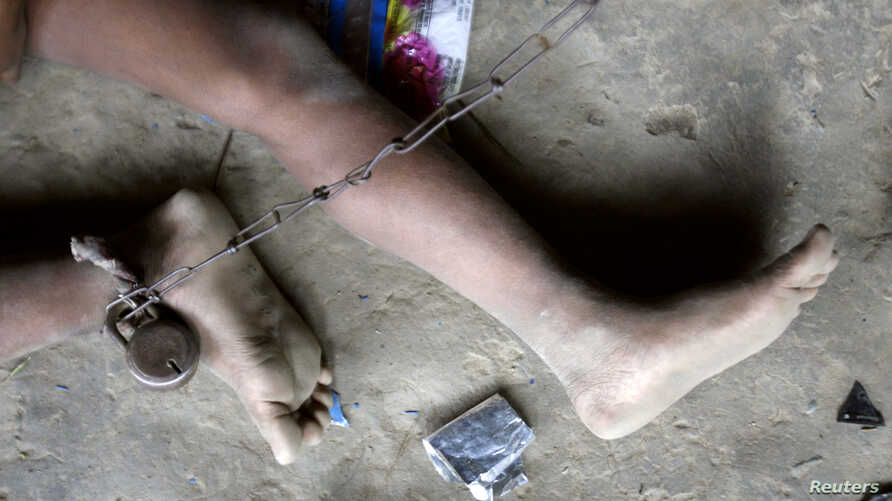 FILE - Mentally challenged Shomvu Sharkar, 8, is chained inside his hut in the northeastern Indian city of Siliguri.