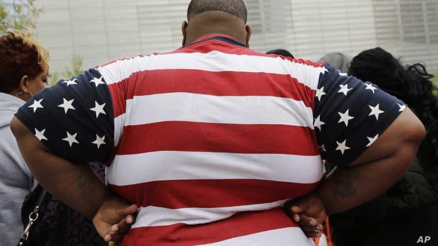 In this Thursday, May 8, 2014 photo, an overweight man wears a shirt patterned after the American flag during a visit to the World Trade Center, in New York.