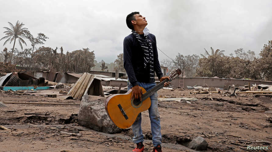 Brian Rivera, who lost 13 members of his family during the eruption of the Fuego volcano, holds his sister's guitar near debris of his home at San Miguel Los Lotes, Escuintla, Guatemala June 7, 2018.