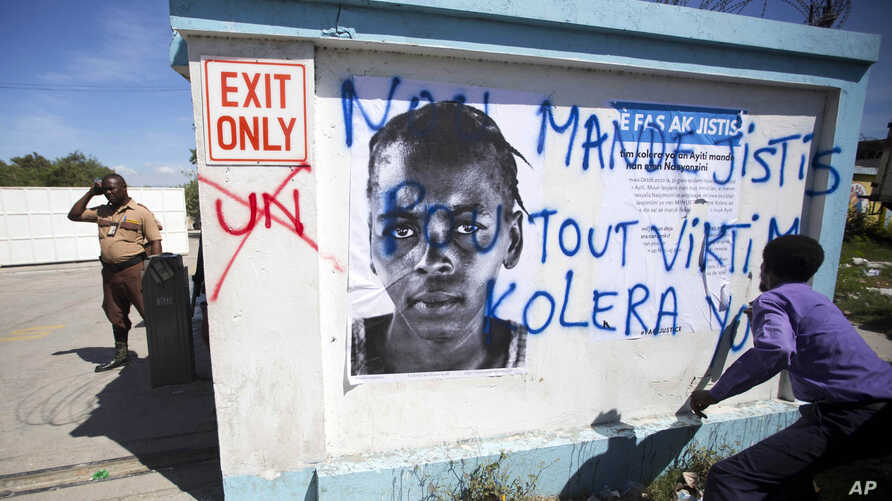 "A demonstrator spray paints the message in Creole ""We demand justice for all cholera victims"" outside United Nations headquarters to protest the U.N. peacekeeping mission in Port-au-Prince, Haiti, Oct. 15, 2015."