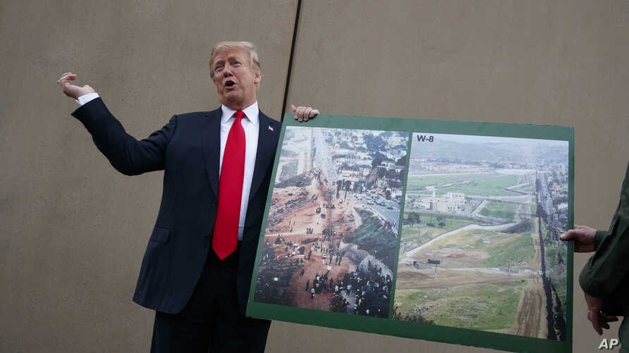 FILE - President Donald Trump talks with reporters as he gets a briefing on border wall prototypes, in San Diego, California March 13, 2018.