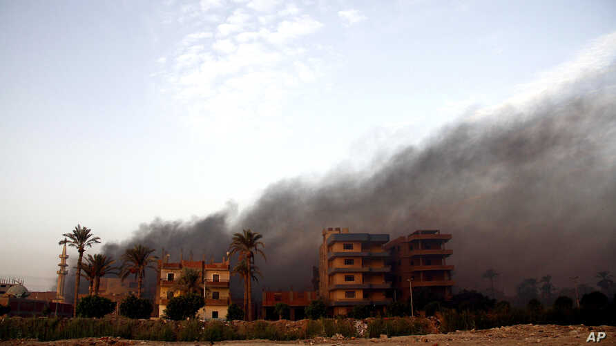 Smoke rises during clashes between Egyptian security forces and suspected militants, not pictured, in the town of Kirdasah, near Giza Pyramids, Egypt, Sept. 19, 2013.