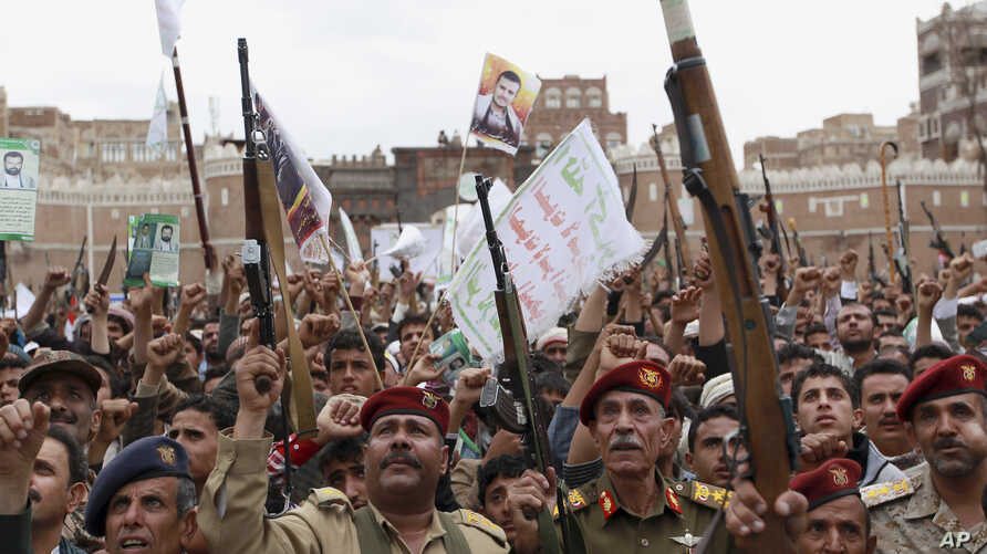 Shiite rebels, known as Houthis, hold up their weapons to protest Saudi-led airstrikes during a rally in Sanaa, Yemen, March 26, 2015.