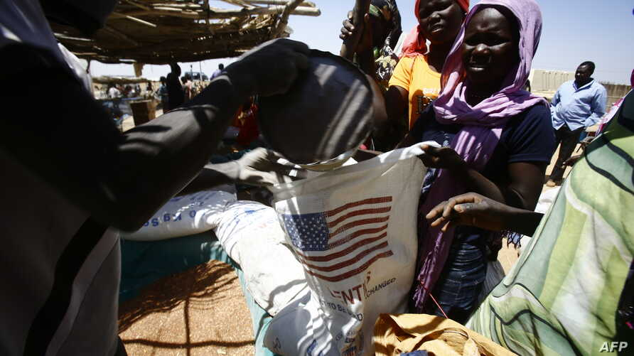 "South Sudanese refugees collect aid food at a ""Refugee Waiting Centre"" in Al-Eligat area along the border in Sudan's White Nile state, Feb. 27, 2017."