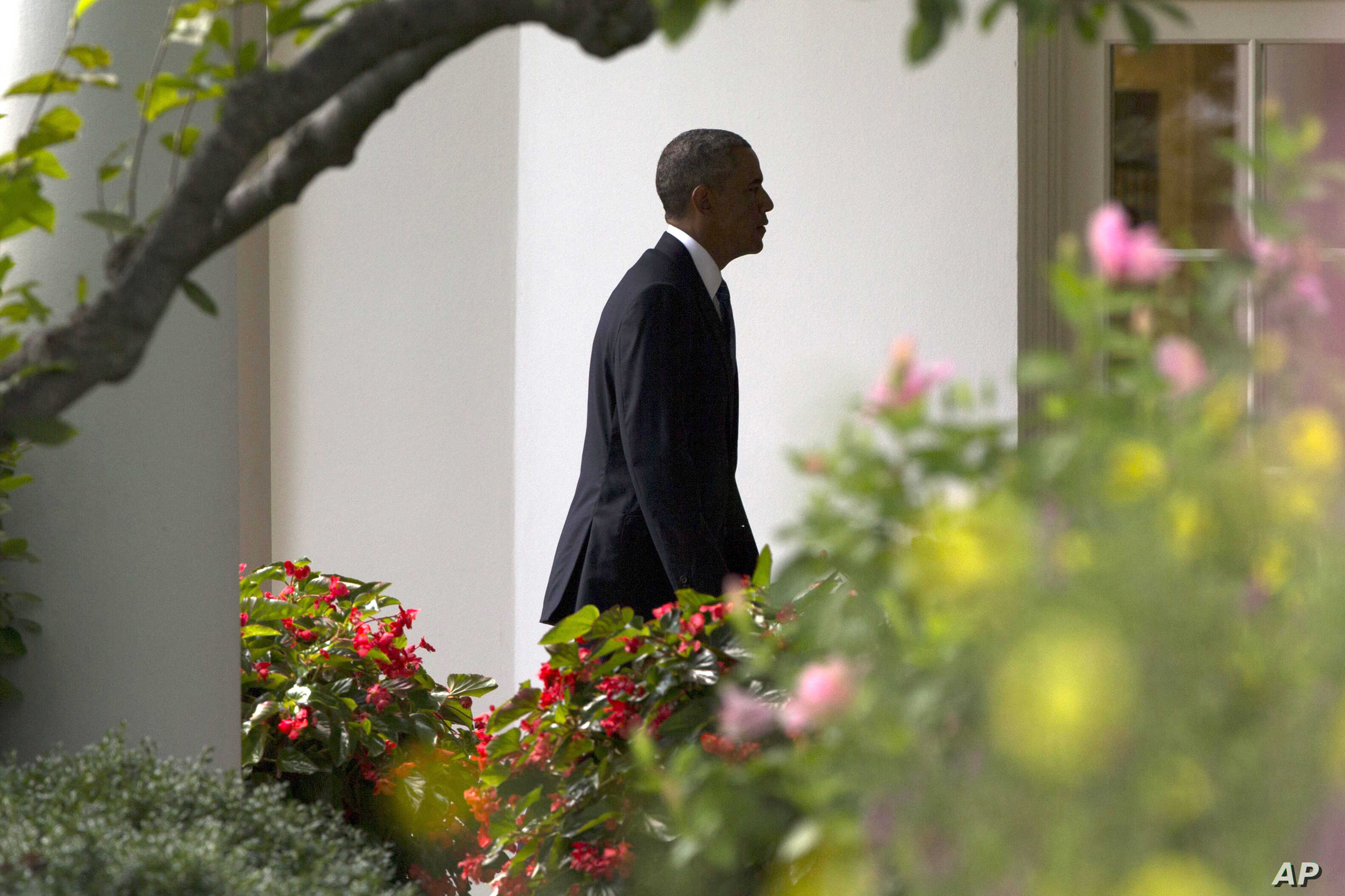 President Barack Obama walks to the Oval Office of the White House in Washington, Aug. 26, 2014.