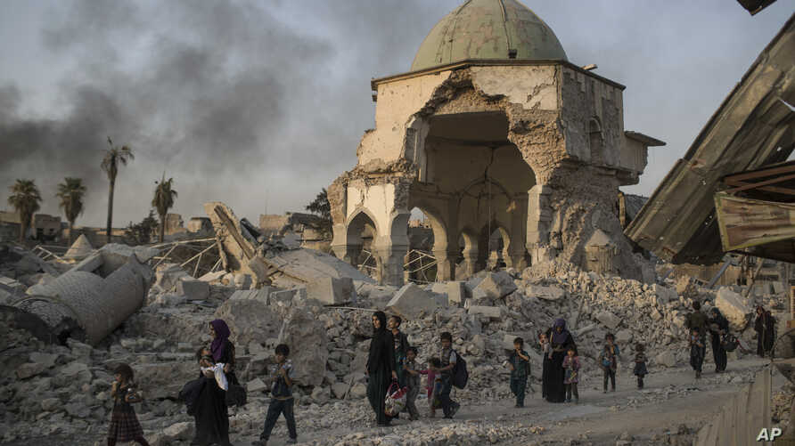 Fleeing Iraqi civilians walk past the heavily damaged al-Nuri mosque as Iraqi forces continue their advance against Islamic State militants in the Old City of Mosul, Iraq, July 4, 2017.