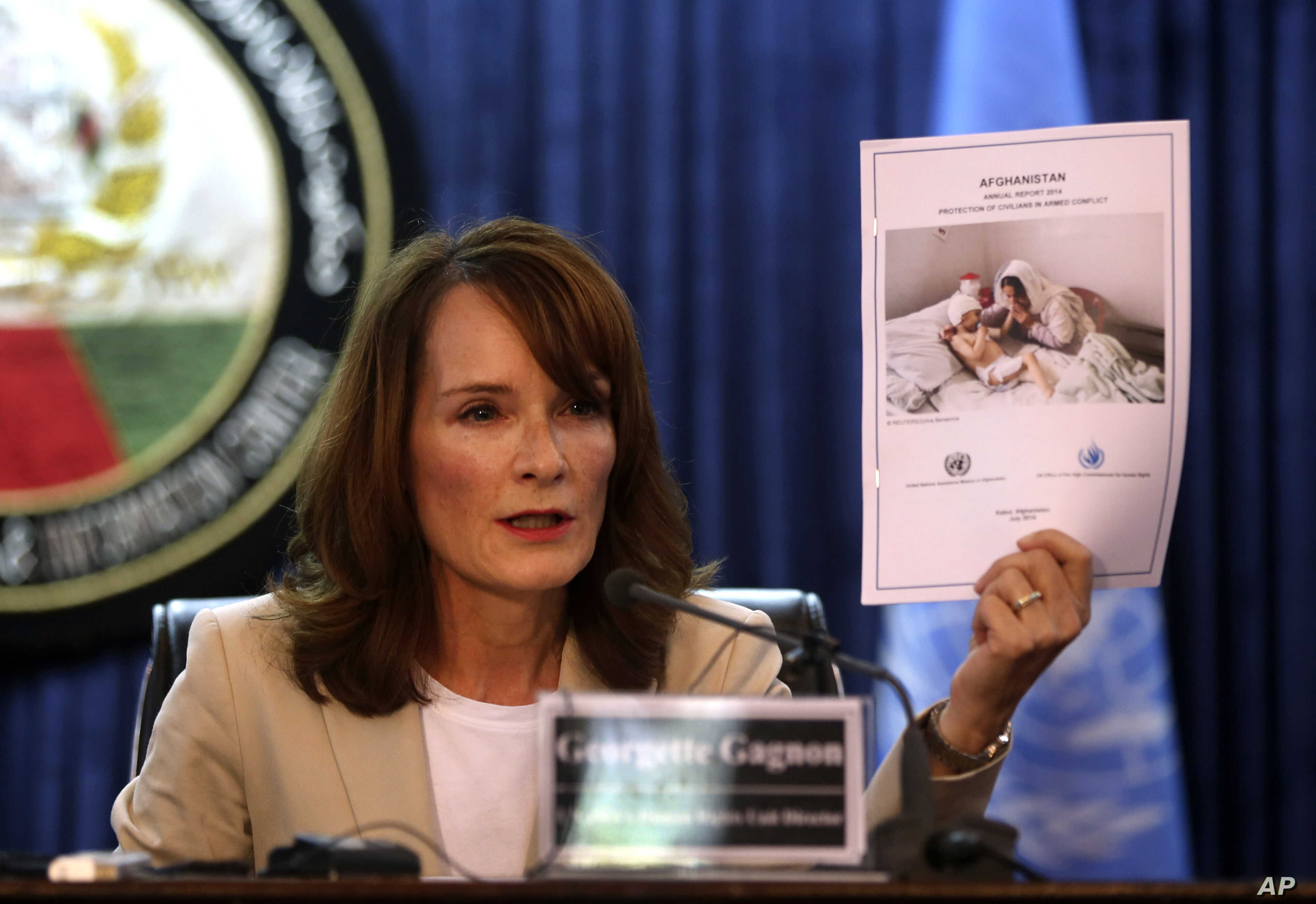 Georgette Gagnon, the director of human rights for the U.N. mission in Afghanistan holds up a copy of a UN report during a news conference in Kabul, Afghanistan, July 9, 2014.
