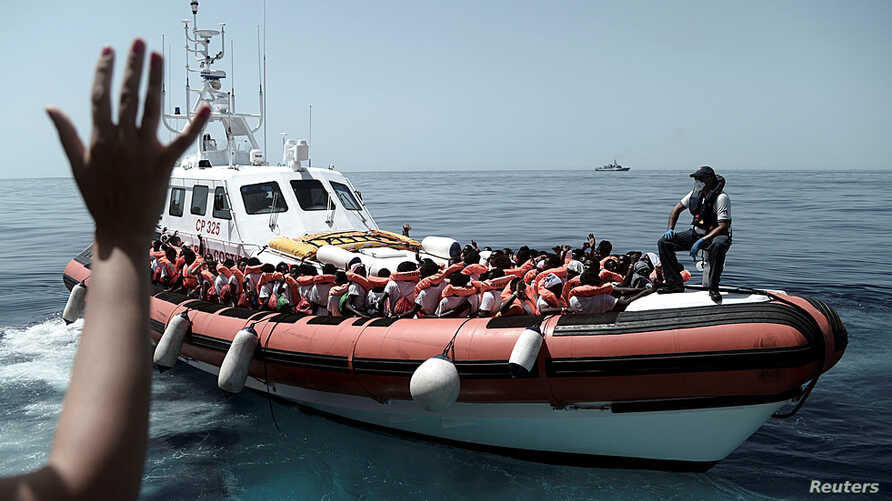 Migrants are seen after being rescued by Aquarius, a ship run in partnership between SOS Mediterranee and Medecins Sans Frontieres in the central Mediterranean Sea, June 12, 2018.