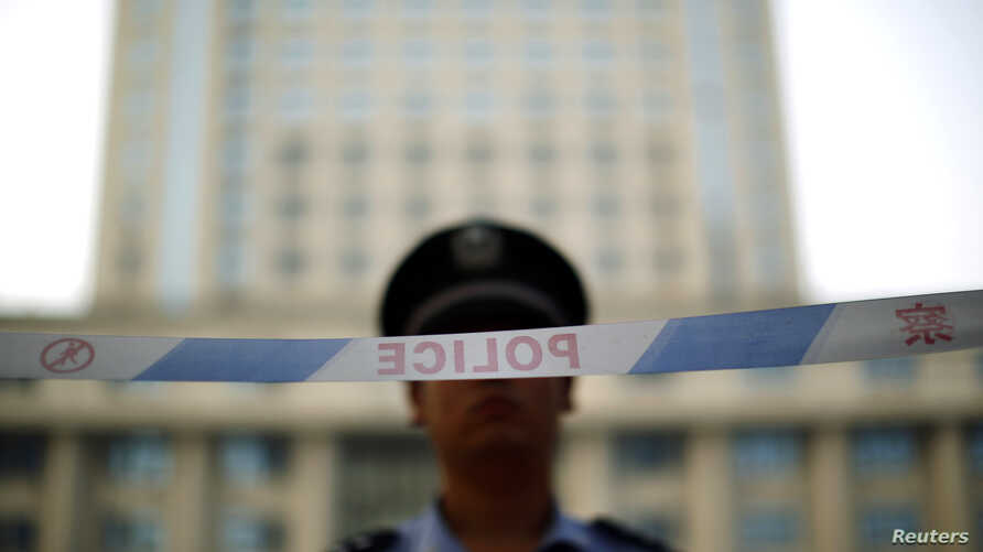 A police officer stands guard at the entrance to the Jinan Intermediate People's Court on the third day of the trial of ousted Chinese politician Bo Xilai in Jinan, Shandong province August 24, 2013. Bo Xilai accepted responsibility for 5 million yua