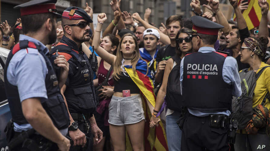 Catalan regional mossos d'esquadra police officers stand between protesters and the national police headquarters during a one-day strike in Barcelona, Oct. 3, 2017.