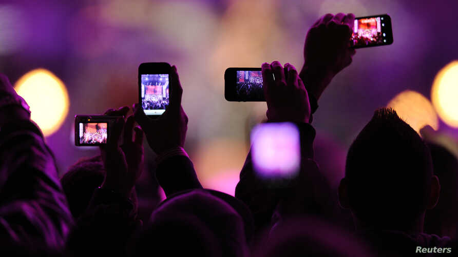 "FILE - Fans take photos with their mobile phones during the VH1 ""Divas Salute The Troops"" show at the Marine Corps Air Station Miramar in San Diego, Dec. 3, 2010."