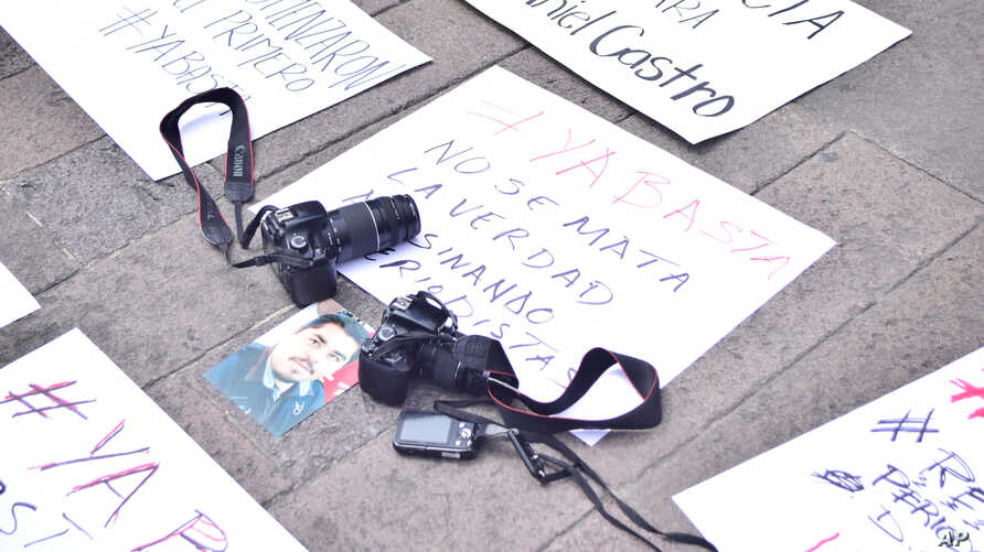 """FILE - Cameras are placed over a placard reading """"You don't kill the truth killing journalists"""" during a protest following the murder of photojournalist Daniel Esqueda in San Luis Potosi, Mexico, Oct. 6, 2017."""