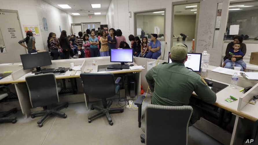 FILE - U.S. Customs and Border Protection agents work at a processing facility in Brownsville,Texas, June 18, 2014. Immigration courts, backlogged by years of staffing shortages and tougher enforcement, were put further behind schedule by the recent