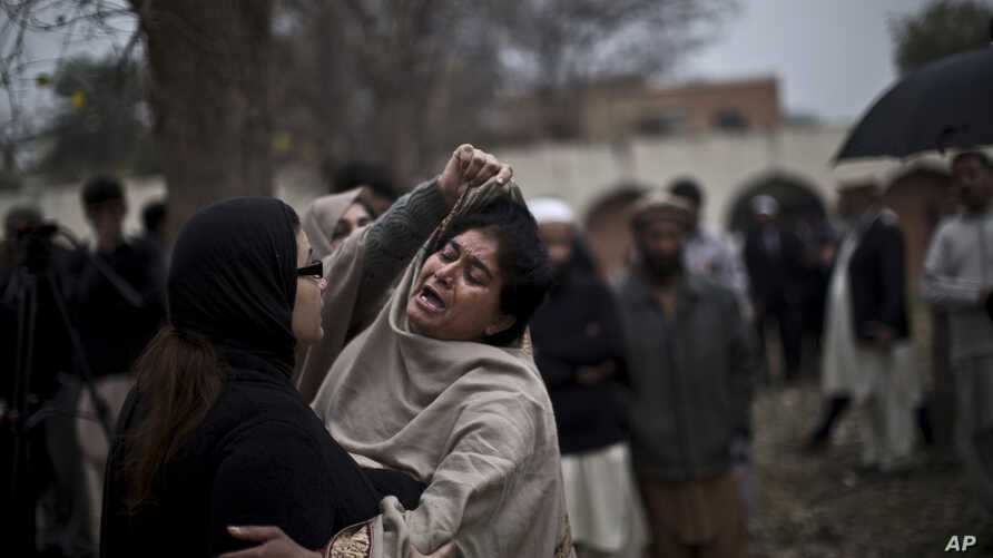 A woman comforts a woman grieving outside a hospital's morgue, where the bodies of victims of a twin suicide bombing were taken, Islamabad, March 3, 2014.