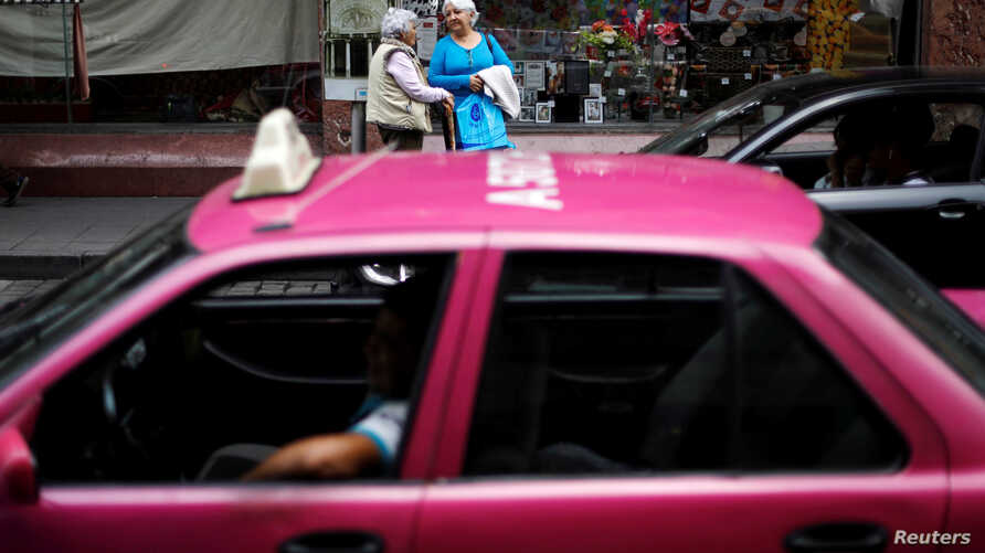 Women wait for public transport in Mexico City, Mexico, Oct. 10, 2018.