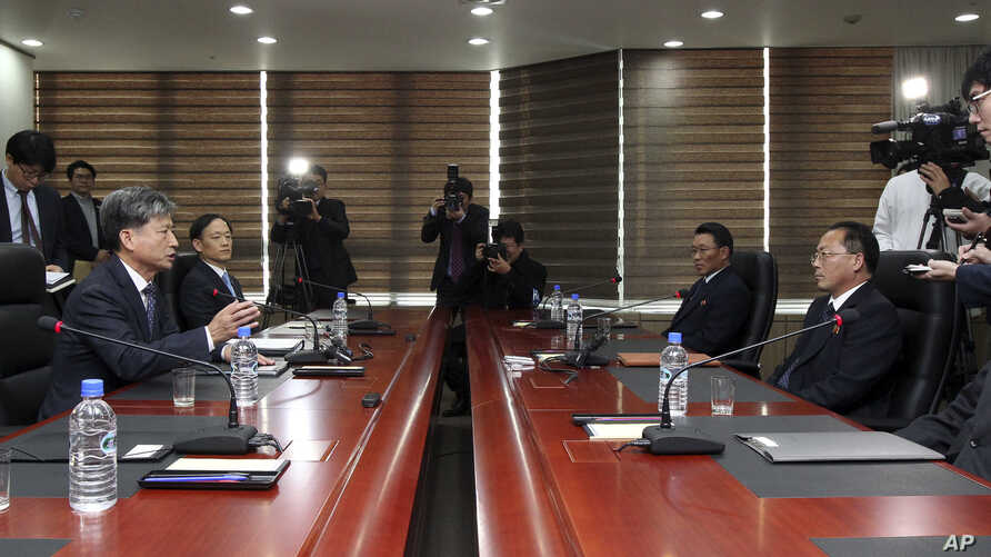 Hwang Boogi, second from left, South Korea's vice minister of unification and the head negotiator for high-level talks with North Korea, talks as his North Korean counterpart Jon Jong Su, second from right, listens during their meeting at the Kaesong