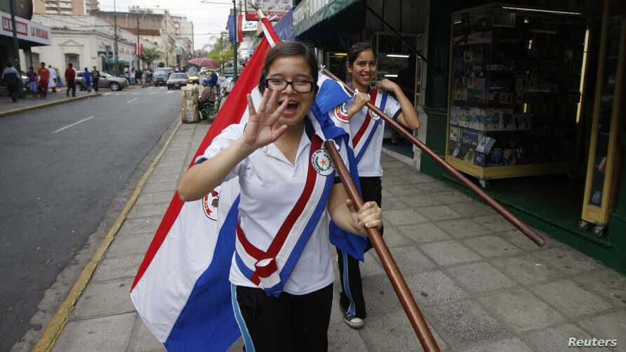 Paraguayan schoolgirls carry flags as they wear sashes a day before the inauguration of President-elect Fernando Lugo's government in Asuncion August 14, 2008.