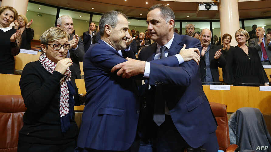 Gilles Simeoni, right, is congratulated by newly elected President of the Corsican Assembly Jean-Guy Talamoni as he celebrates after being elected president of the Corsican Executive Council in the Corsican Assembly in Ajaccio, on the French Mediterr