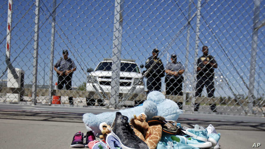 FILE- Shoes and a teddy bear, brought by a group of U.S. mayors, are piled up outside a holding facility for immigrant children in Tornillo, Texas, near the Mexican border, June 21, 2018.