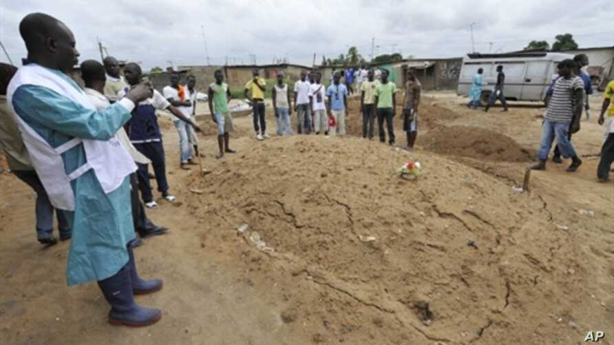 An Ivorian Red Cross worker photographs an area claimed to be a mass grave on May 4, 2011 during a mission to collect corpses in Yopougon, a district to the west of Abidjan.