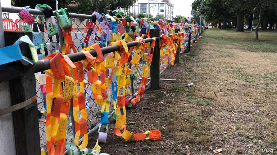 Paper links are draped over the fence at Hagley Park near one of the mosques were more than 40 people were killed in Christchurch March 15. (S. Miller/VOA)