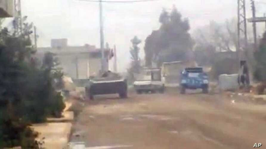 In this image from amateur video made available by the Ugarit News group purports to show military vehicles in Homs, Syria, December 21, 2011.