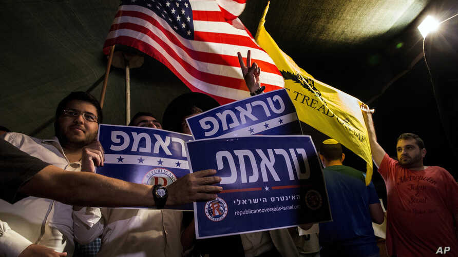 Mideast Israel Trump: Israelis wave flags and hold signs during a rally, sponsored by Republicans Overseas Israel, a local organization that encourages American expatriates to cast absentee ballots for Republican presidential candidate Donald Trump, ...