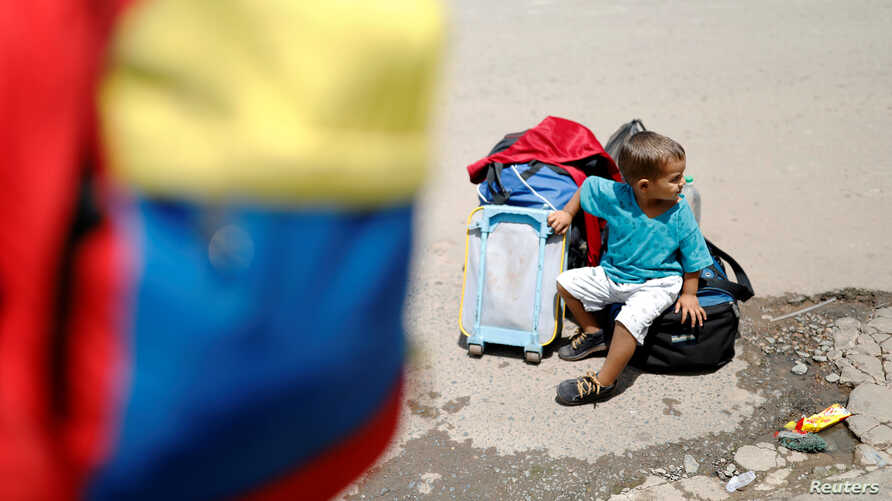 A Venezuelan boy sits next to family belongings at the Pacaraima border control, Roraima state, Brazil, Aug. 20, 2018.