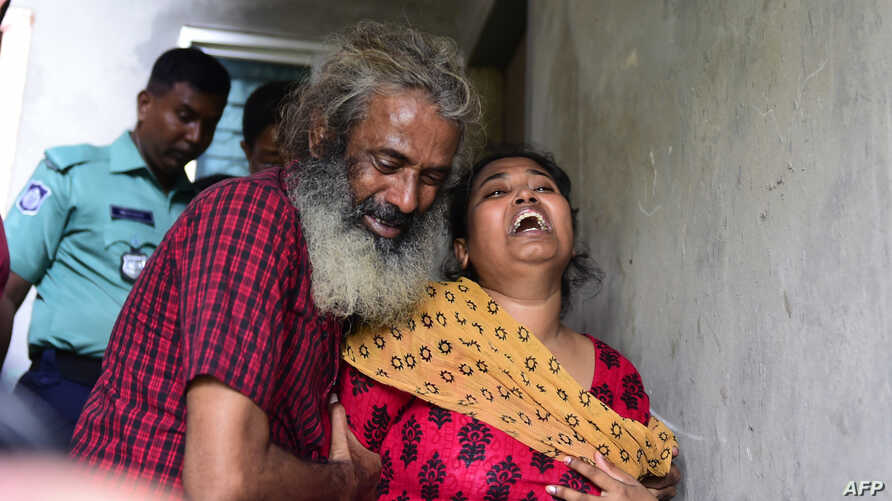 Asha Moni, right the wife of murdered Bangladeshi blogger Niloy Chakrabarti who wrote under the name Niloy Neel, weeps outside her home in Dhaka on August 8, 2015.