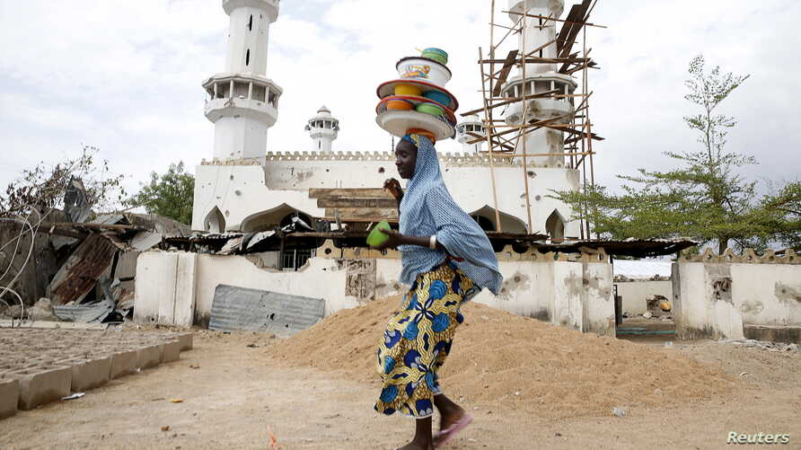 A girl walks past a destroyed mosque in the town of Mararaba, after the Nigerian military recaptured it from Boko Haram, in Adamawa state, May 10, 2015.