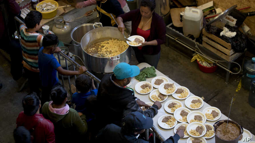 Breakfast of rice, beans and tortilla chips is prepared for Honduran migrants inside an empty warehouse that opened its doors to migrants in downtown Tijuana, Mexico, Dec. 18, 2018. The owner opened the warehouse for two months, after it had been emp