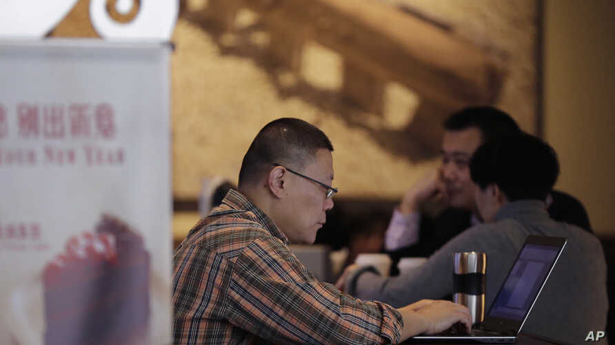 FILE - A man surfs Internet on his laptop computer at a cafe in Beijing, China, Feb. 16, 2015.
