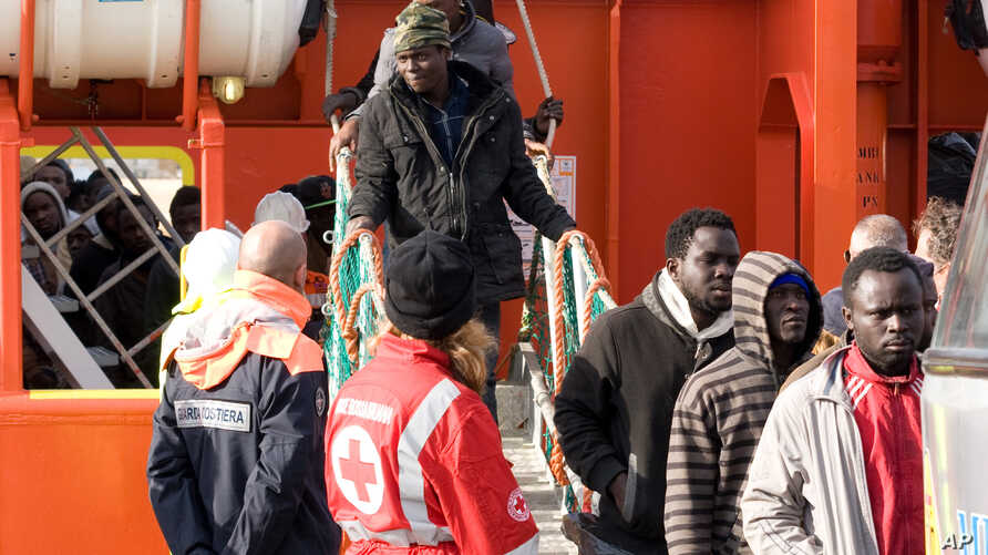 Migrants disembark from a tug boat after being rescued in the harbor of Lampedusa, Italy, Feb. 16, 2015.