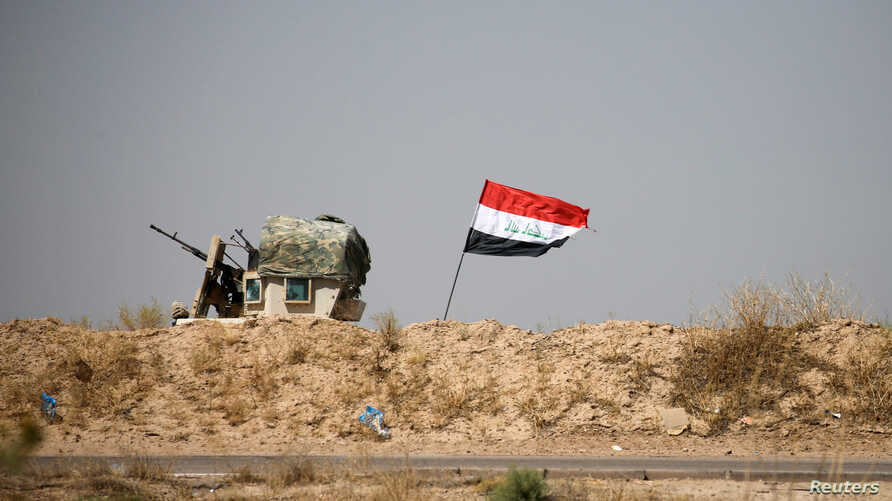 A military vehicle of the Iraqi security forces is seen next to an Iraqi flag in Falluja, Iraq, June 13, 2016. An operation to liberate the city from Islamic State militants is now in its thrid week.