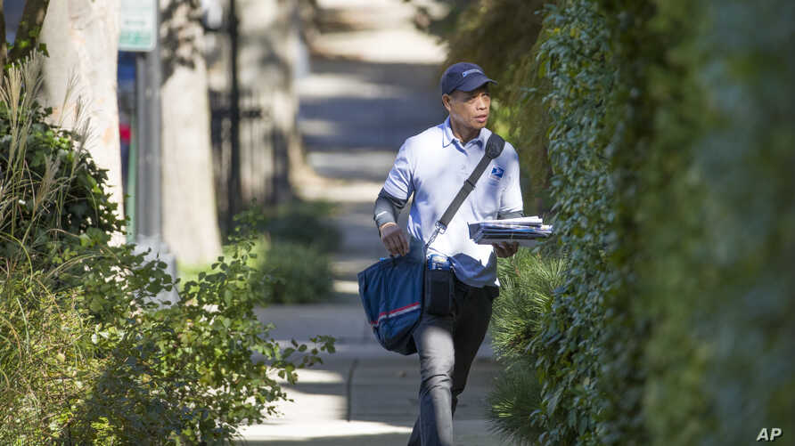 FILE - A letter carrier with the U.S. Postal Service makes his rounds near the home of former president Barack Obama, Oct. 24, 2018, in Washington.