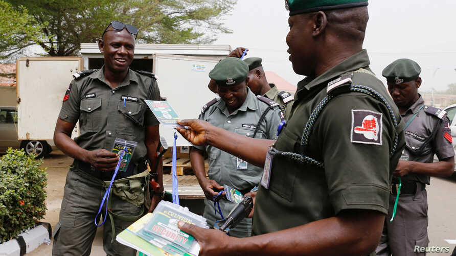 A police officer hands out security tags during the distribution of election materials at the INEC office in Yola, Adamawa State, ahead of the country's presidential election, in Yola, Nigeria, Feb. 15, 2019.