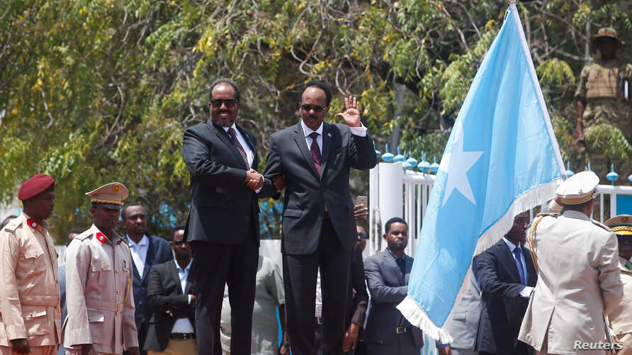 Somalia's newly elected President Mohamed Abdullahi Mohamed (right) flanked by outgoing president Hassan Sheikh Mohamud (left) attends a military parade during the hand-over ceremony at the Presidential palace in Somalia's capital Mogadishu, Feb. 16,