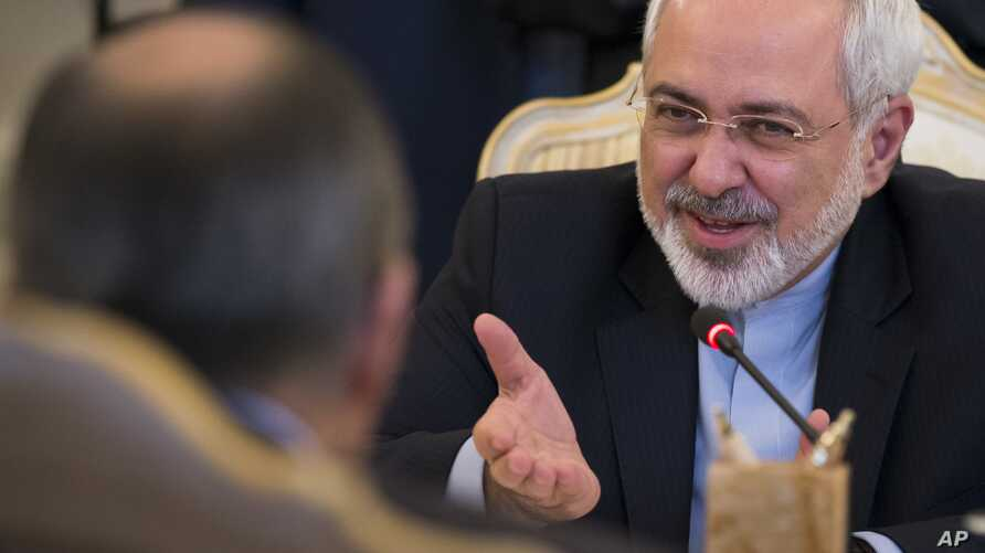 Iranian Foreign Minister Mohammad Javad Zarif, right, speaks to Russian Foreign Minister Sergey Lavrov, back to a camera, during their meeting in Moscow, Aug. 29, 2014.