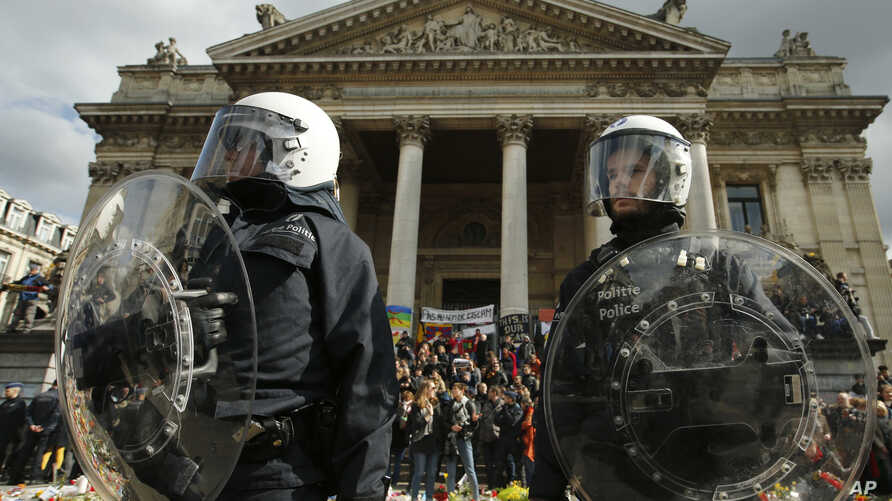 Police in riot gear protect one of the memorials to the victims of the recent Brussels attacks, as right wing demonstrators protest near the Place de la Bourse in Brussels, March, 27, 2016.