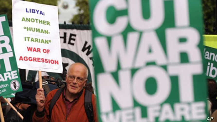 Protesters hold placards as they protest against the British government's involvement in the bombings of Libya, during a demonstration outside Downing street in central London, May 16, 2011