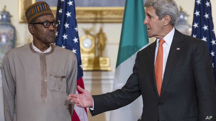 Secretary of State John Kerry gestures while he and Nigerian President Muhammadu Buhari make statements prior to a working lunch at the State Department in Washington, July 21, 2015.