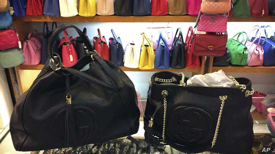 Counterfeit branded bags appear on display in a room hidden from the public area of a popular shopping mall in Beijing, China, March 11, 2015.
