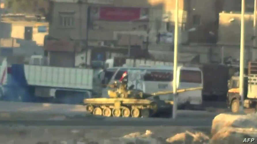 An image grab taken from a video uploaded on YouTube on August 22, 2012 allegedly shows a Syrian army tank deploying the the Nahr Aishe neighborhood of Damacus on August  22, 2012. Syrian forces have killed dozens of civilians in a raid on a Damascus