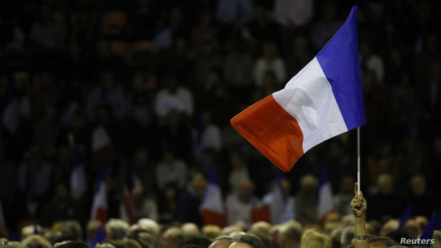 "A supporter raises a French flag as Nicolas Sarkozy, former head of the ""Les Republicains"" political party and candidate for the French center-right presidential primary, attends a campaign rally in Nimes, France, Nov. 18, 2016."